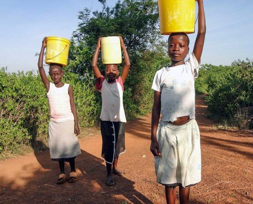 Children carrying 5 gallon buckets full of water