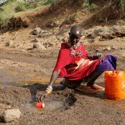 Maasai woman at water puddle