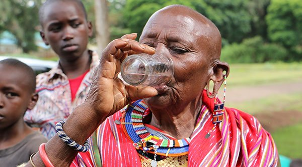 Maasai woman drinking clean, filtered water