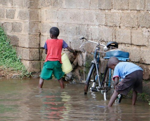 Boys washing a bike and collecting water